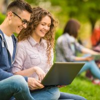 Couple of attractive smiling students dressed casual having fun outdoors on campus at the university.