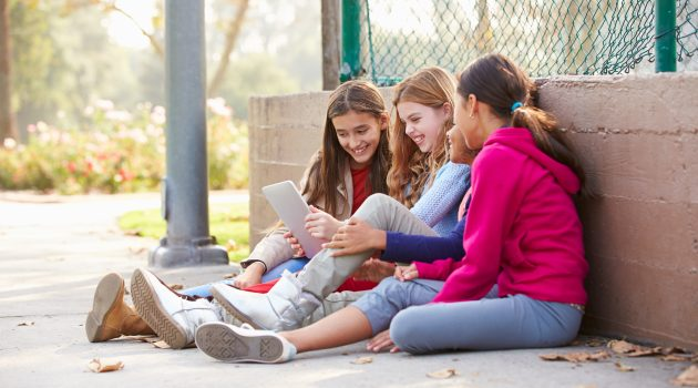 Group Of Young Girls Using Digital Tablet In Park