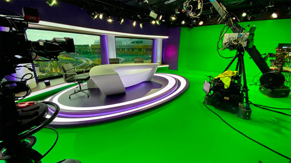 """El plató real fue ampliado mucho más allá de sus límites físicos, habilitando nuevos espacios virtuales y creando un estudio circular 360. MOOV, compañía líder en grafismo deportivo y de eventos con sede en Reino Unido, renovó totalmente el estudio de BBC Sport en Wimbledon, ofreciendo a la vez nuevas formas de interacción con la audiencia, potenciando así la capacidad narrativa durante el torneo. Para ello, en lugar de reconstruir el plató físico, MOOV y BBC Sport decidieron virtualizarlo para aprovechar las infinitas posibilidades que ofrece la tecnología virtual. La compañía trabajó con Brainstorm para proveer el plató virtual y las más avanzadas funciones de Realidad Aumentada disponibles en el mercado, basadas en la solución de estudio virtual InfinitySet, y utilizando el motor Unreal Engine de Epic Games. Creado en torno a un estudio de croma, el plató virtual de Wimbledon amplió de forma espectacular el espacio disponible más allá de sus límites físicos, habilitando nuevos espacios alrededor de la mesa real, lo que en efecto creaba un estudio circular de 360º. También permitió tiros de cámara alternativos, más espacio para añadir infografías y, por supuesto, mayor presencia de la marca Wimbledon. InfinitySet aportó como valor añadido su flexibilidad para cambiar, adaptar y hacer ajustes de última hora. """"Conseguimos crear un espacio virtual que permitía una cobertura dinámica del torneo combinando a la perfección imágenes reales y virtuales, mejorando significativamente la cobertura y que supuso un aumento del interés de la audiencia"""", afirma Nev Appleton, director y cofundador de MOOV. """"Ha sido un proyecto especialmente difícil, no sólo por las limitaciones de tiempo, sino también por las restricciones de personal in situ y por cuestiones técnicas como la necesidad de reutilizar el estudio para los resúmenes diarios. Pero a pesar de los retos, los resultados, realmente magníficos, reforzaron nuestra apuesta de utilizar la tecnología virtual para mejorar los p"""